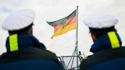 """Zwei Marinesoldaten stehen am 8. Februar 2020 amHafen des Marinestützpunktes Wilhelmshaven und beobachten die Rückkehr der Fregatte """"Hmburg"""" von einem Mittelmeereinsatz, zwischen ihnen ist die deutsche Flagge, die auf dem Heck der Fregatte angebracht ist, zu sehen. (picture alliance / Mohssen Assanimoghaddam)"""