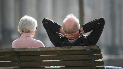 Ein Rentnerpaar sitzt auf einer Bank vor dem Reichstag und sonnt sich (picture alliance / Stephan Scheuer)