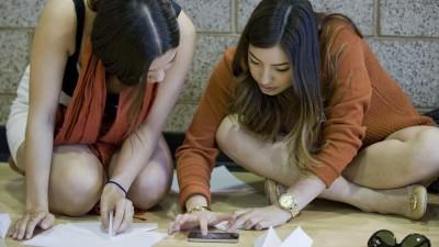 Die Studentinnen Erin Maudlin und Frances Yoshikane sitzen auf dem Boden und gucken ein Youtube-Video auf einem Smartphone, um die Anleitung für eine Aufgabe zu erhalten. (imago/ZUMA Press)