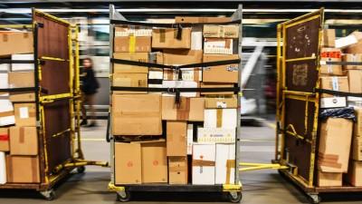 Pakete werden am 30.11.2017 auf Transportwagen durch die Halle des DHL-Paketzentrums in Rüdersdorf (Brandenburg) gefahren. Ran an die Päckchen und Pakete: Für die Mitarbeiter von Paketzentren heißt es jetzt wieder Ärmel hochkrempeln. Zum Beispiel am DHL-Standort im brandenburgischen Rüdersdorf (Märkisch-Oderland). Bis zu 400 000 Pakete können hier vor Weihnachten täglich bearbeitet werden, wie es vom Unternehmen heißt. Foto: Patrick Pleul/dpa-Zentralbild/ZB | Verwendung weltweit (dpa-Zentralbild)