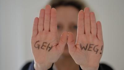 """Symbolfoto: Eine Frau steht mit ausgestreckten Armen da, auf ihren Händen steht geschrieben """"Geh weg!"""" aufgenommen am 23.02.2016 in Osterode. (dpa / picture alliance / Frank May)"""