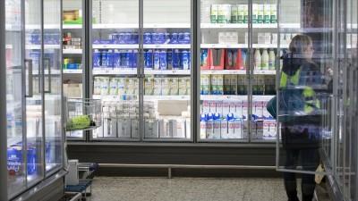 Eine Frau steht in einem Einkaufsmarkt vor einem Kühlregal mit Milchprodukten. (dpa / Friso Gentsch)