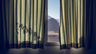 Durch ein Fenster mit fast ganz zugezogenen, grünen Vorhängen lässt sich eine bergige Landschaft erkennen. (imago images / Westend61 / Maria Maar)