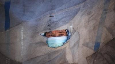 Der Kopf eines Mannes mit Schutzmaske schaut aus einem Loch einem Stück Stoff hervor. (imago / INA Photo Agency / Yousef Masoud)