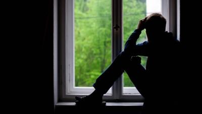 Ein Mann sitzt an einem Fenster und schaut raus (imago/stock&people/Thomas Eisenhuth)
