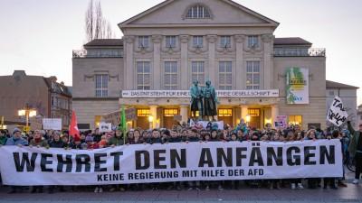 """""""Wehret den Anfängen - Keine Regierung mit Hilfe der AFD"""" steht auf einem Transparent, das Demonstranten vor dem Theater und dem Goethe- und Schillerdenkmal halten. Die Menschen demonstrieren gegen den neuen Ministerpräsidenten von Thüringen. (dpa / Johannes Krey)"""