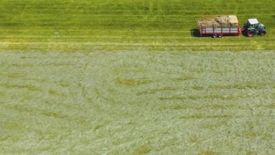Luftbild von einem Landwirt, der mit seinem Traktor über eine Wiese fährt. (imago / Eibner Europa)