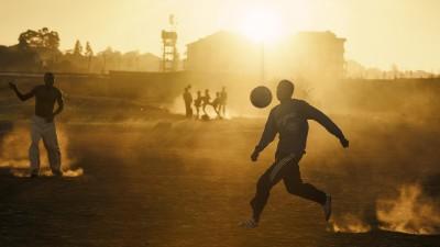 Jugendliche spielen im warmen abendlichen Gegenlicht Fußball in einem Slum Nairobis. (laif / Christoph Goedan)