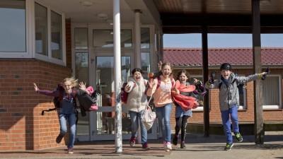 Glückliche Schüler laufen lachend nach Unterrichtsendeauseinem Schulgebäude. (imago images / imagebroker / Siegfried Kuttig)