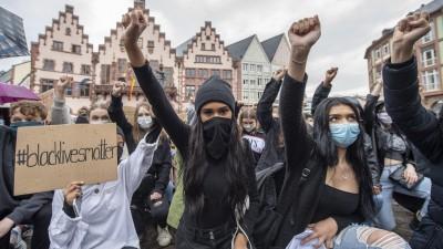 Auf Knien und mit in die Höhe gestreckter Faust bekunden Demonstrantinnen auf dem Römerberg in Frankfurt ihre Solidarität mit den Anti-Rassismus-Protesten in den USA. (dpa/ Boris Roessler)