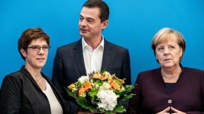 Mike Mohring, Landesvorsitzender der CDU in Thüringen, steht mit seinem Blumenstrauß zwischen Annegret Kramp-Karrenbauer (l.), Bundesvorsitzende der CDU und Verteidigungsministerin, und Bundeskanzlerin Angela Merkel (CDU). (dpa / Michael Kappeler)