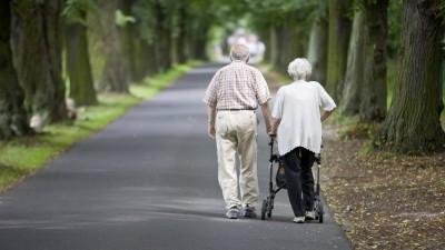 Ein Ehepaar geht in Potsdam eine Allee entlang. Die Frau schiebt einen Rollator. (imago/Thomas Trutschel)