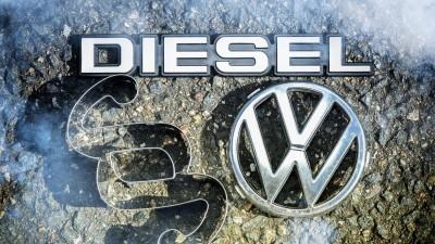 Ein VW-Logo, Paragrafen- und Dieselzeichenliegen auf der Straße. (imago)