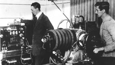 Auf einer historischen Fotografie sind zwei Männer zu sehen, die an technischen Geräten beschäftigt sind. (Förderverein Sender Königs Wusterhausen / Archiv)