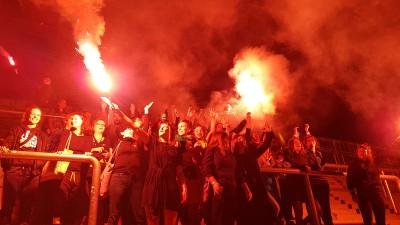 """Weibliche Ultrafans aus ganz Europa zur Eröffnung der Ausstellung """"Fan.Tastic Females"""". Eine Gruppe Frauen steht in einem Fußballstadion, das durch Feuer beleuchtet wird. (Foto: Alexander Berthold)"""