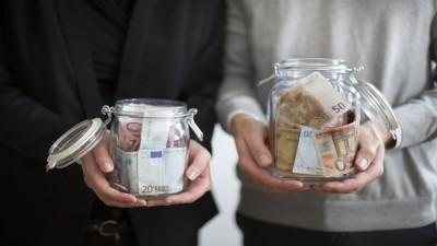 Symbolbild zum Thema Equal Pay Day / Gender Pay Gap / Entgeltgleichheit. Mann und Frau halten unterschiedlich grosse Glaeser gefuellt mit Geldscheinen in den Haenden. Berlin, 14.05.2013. Berlin Deutschland *** Symbol image on the subject of Equal Pay Day Gender Pay Gap Equal pay Men and women hold glasses of different sizes filled with banknotes in their hands Berlin 14 05 2013 Berlin Germany PUBLICATIONxINxGERxSUIxAUTxONLY Copyright: xUtexGrabowsky/photothek.netx (imago images │photothek)