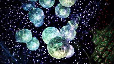 Das Bild zeigt mehrere silberne Diskokugeln vor dunklem Hintergrund, der von Lichtreflexen der Kugeln durchsetzt ist. (unsplash.com; Fidel Fernando)