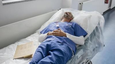 Ein erschöpfter Arzt liegt auf der Liege in einem Krankenhausflur und schläft. (imago / fStop Images / Halfdark)