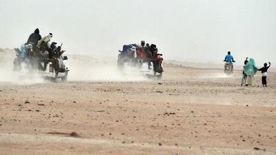 Mehrere Pick-ups, auf denen dutzende Migranten sitzen, fahren durch die Wüste von Agadez im Niger in Richtung Liyben (1.6.2015). (afp / Issouf Sanogo)