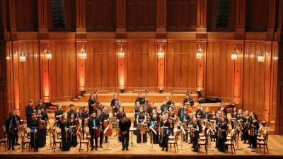Junge Musiker stehen auf einer hell erleuchteten Bühne. (Deutsche Streicherphilharmonie / VdM)