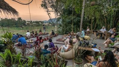 Vorwiegend westliche Backpacker entspannen beim Abendlicht auf der Terrasse einer Bar am Flussufer. (picture alliance / Juergen Held)