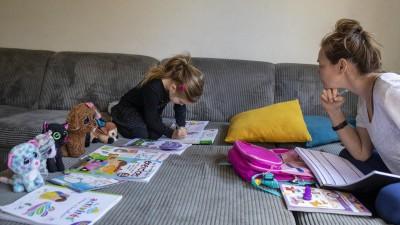 Abby, 6, mit ihrer MutterLisa beim Homeschooling auf dem Sofa zu Hause.Die Kuscheltiere sitzen auch alle vor einem Arbeitsheft. 20. März 2020 in Claira,Frankreich. (Getty / Corbis News / Tim Clayton)