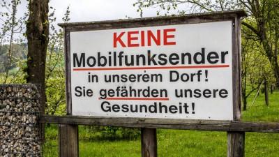 Auf einem Protestschild steht: Keine Mobilfunksender in unserem Dorf! Sie gefährden unsere Gesundheit! (imago images / Michael Eichhammer)