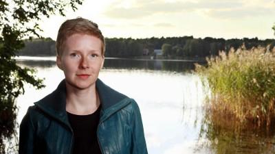 Die Autorin Judith Zander sitzt vor einem See und schaut in die Kamera. (Imago / Gezett)