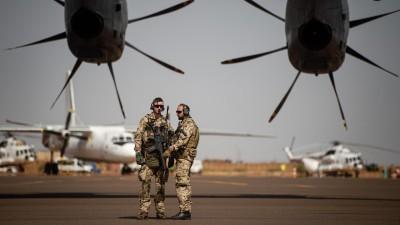 Deutsche Soldaten stehen am Flughafen in Gao und sichern ein Transportflugzeug. (picture alliance / Arne Immanuel Bänsch)