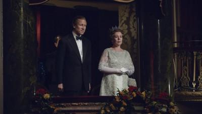 """Szenenbild aus der 4. Staffel der Netflix-Serie """"The Crown"""", bei dem Tobias Menzies als Prinz Philip und Olivia Colman als Queen Elisabeth II. in der königlichen Loge eines Theaters stehen. (imago images / Alex Bailey /  Netflix / The Hollywood Archive / Cinema Publishers Collection)"""