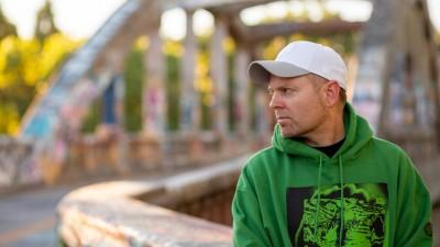 DJ Shadow zur Seite blickend, mit grünem Hoodie und weißem Basecap; im Hintergrund eine Brücke (Derick Daily)