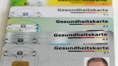 Gesundheitskarten verschiedener Krankenkassen liegen auf einem Tisch (dpa / Jens Kalaene)