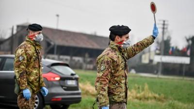 Ein Soldat mit Atemschutzmaske hält an einer Straßensperre vor der roten Zone von Turano Lodigiano eine Winkerkelle in die Höhe. (Claudio Furlan/LaPresse/ZUMA Press/dpa )