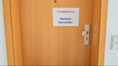 """Das Foto zeigt eine Wohnungstür, an der ein Schild """"Vorsicht. Häusliche Quarantäne"""" hängt. (Imago/ KS-Images)"""