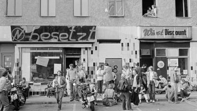 Schwarz-Weiß-Bild einer Hausbesetzung in Kreuzberg in den 80er-Jahren. Menschen sitzen und stehen vor einem besetzten Haus. (picture alliance/akg-images)
