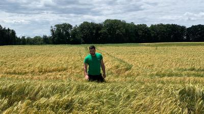 Ein dunkelhaariger Mann mit grünem T-Shirt steht in einem Kornfeld. (Uschi Götz)