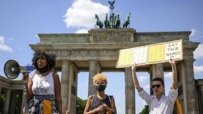 """Aktivisten vor dem Brandenburger Tor halten ein Schild mit der Aufschrift """"Say Their Names"""" in die Höhe. (Imago / ZUMA Wire / Omer Messinger)"""