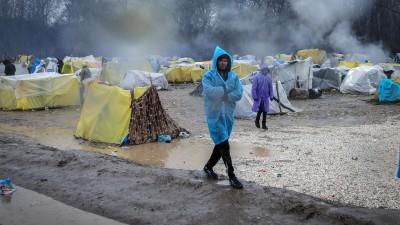 Zwei Männer im Regenponcho gehen durch ein notdürftiges Zeltlager von Flüchtlingen. (picture alliance/dpa/NurPhoto/Belal Khaled)