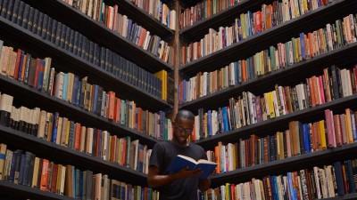 Ein Mann steht vor einem großen Bücherregal und liest. (Eyeem / Valerie Briee)