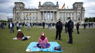 Polizisten fordern eine meditierende Frau während einer sogenannten Hygienedemo vor dem Reichstagsgebäude in Berlin auf, den Platz zu verlassen. (imago images / IPON / Stefan Boness)