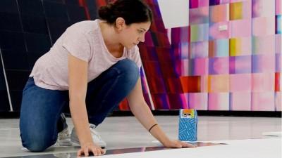 Die 1983 in Beirut geborene Caline Aoun hockt über ihrer Arbeit: Im Hintergrund hängen ihre Drucke an der Wand (Luis Do Rosario)