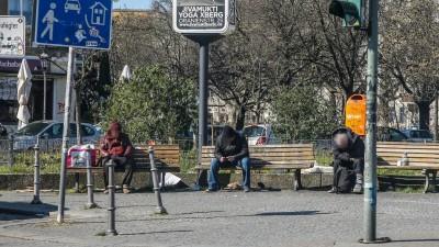 Drei Obdachlose sitzen in Berlin mit großem Abstand auf Parkbänken auf einem Platz in Kreuzberg. (Imago)