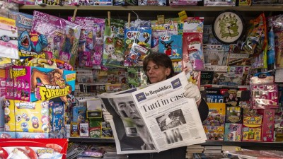 """Eine Zeitungsverkäuferin in einem Kiosk in Italien hält einen Zeitungstitel hoch:""""Tutti a casa"""" (""""Jeder zu Hause"""") in Salerno, Italien am 10.März 2020 (Getty / Ivan Romano)"""