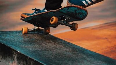 Ein Skateboard mit Füßen darauf, beim Ausführen eine Tricks. (Unsplash / Shawn Henry)