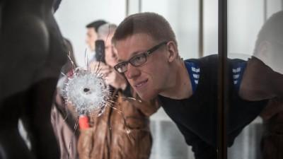 Ein Besucher betrachtet ein Einschussloch in einer Museumsvitrine. (Picture Alliance / AA / Amine Landoulsi)