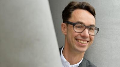 Hinter einem grauen Pfeiler schaut ein Mann mit dunklen zurückgekämmten Haaren und großer Brille und einem freundlichen Gesicht hervor. Er trägt ein weißes Hemd und eine Anzugjacke. (picture alliance / Frank May)