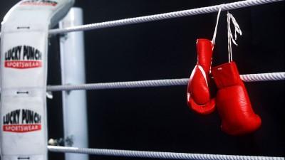 Boxhandschuhe hängen über das Seileines Boxrings. (picture-alliance / ASA / Stefan Matzke)