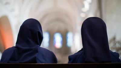 Zwei Ordensschwestern sitzen im Dom.  (dpa / Rolf Vennenbernd)