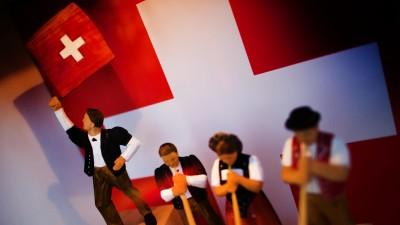 An einem Infostand des Partnerlandes Schweiz auf der Leipziger Buchmesse in Leipzig (Sachsen) stehen am 12.03.2014 Holzschnitzfiguren in einer Glasvitrine. Vom 13. bis 16. März präsentieren sich auf der Messe 2000 Verlage mit ihren Neuerscheinungen. Foto: Arno Burgi/dpa (picture alliance / dpa )