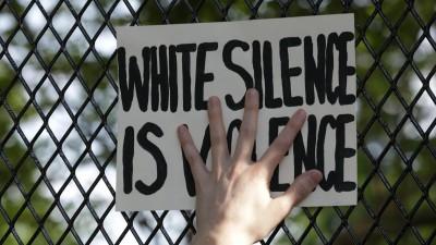 """Eine Hand presst ein Schild mit der Aufschrift """"White Silence is Violence"""" an einen Zaun. (Getty Images / Anadolu Agency / Yasin Ozturk)"""
